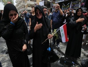 Iraqi women react as people gather at the site of a suicide-bombing attack which took on July 3 in Baghdad's Karrada neighbourhood. Picture: Ahmad al-Rubaye / AFP