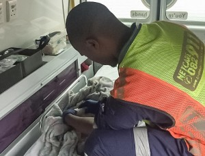 A medic checks on a baby born on a Durban freeway