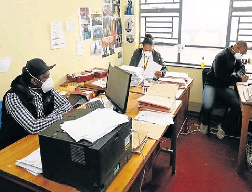 COVER-UP: Detectives wear medical masks in their offices at the Bethelsdorp police station. The multimillion-rand upgrade of the building has been delayed due to ongoing strikes by workers. Picture: EUGENE COETZEE