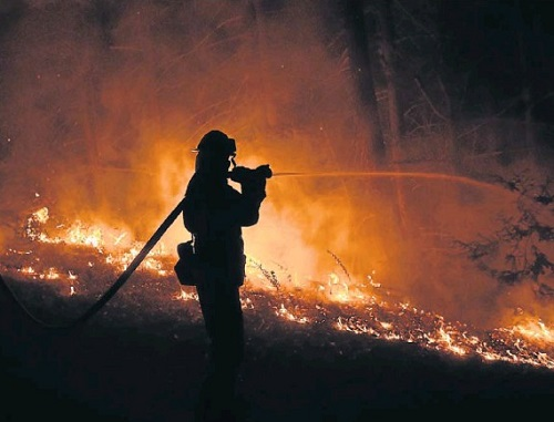 HUGE CHALLENGE: A firefighter helps battle the blaze near Big Sur in California. Picture: REUTERS