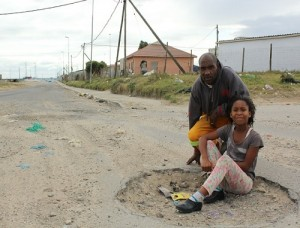 Weekend Post reported potholes across Nelson Mandela Bay, with some being fixed while others received no attention. Ahlumile Mabetha, 8, and her father Xhanti, 45, show the worst section of Tyinira Street, Motherwell, where cars drive next to the road to avoid multiple potholes  Picture: Riaan Marais