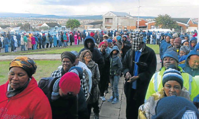 PATIENT VOTERS: Hundreds of northern areas residents queued for hours in the rain outside the Booysen Park Community Hall. Picture: TREMAINE VAN AARDT