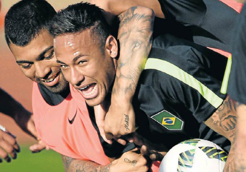 JOKES ASIDE: Brazilian footballers Neymar, right, and Gabriel Jesus have fun at a training session at the Fire Department Training Centre in Brasilia. Picture: AFP