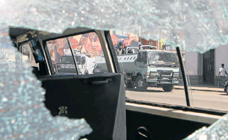 CLAMPING DOWN: Anti-riot police are seen through a broken car window after they clashed with protesters in Harare yesterday. Picture: REUTERS