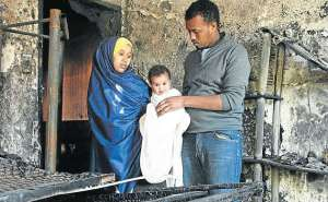 OUT IN THE COLD: Fire victim Riyan Abdi Rahmon, six months, with his mom Shukri Abdi and dad Abdul Rahman Husen Picture: FREDLIN ADRIAAN